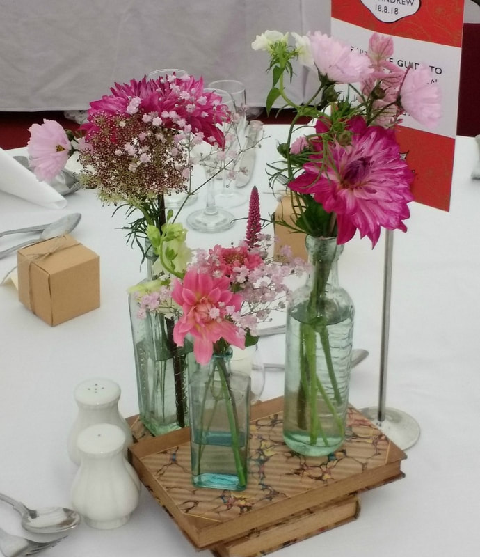 Table decor of vintage glass bottles & summer flowers grown in Scotland for a country wedding