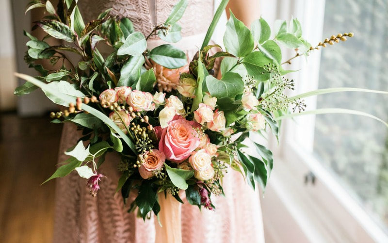 Frontfacing bridal bouquet in peach & coral shaeds with foliage