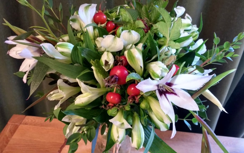 Bridal bouquet of white alstroemeria & red rose hips