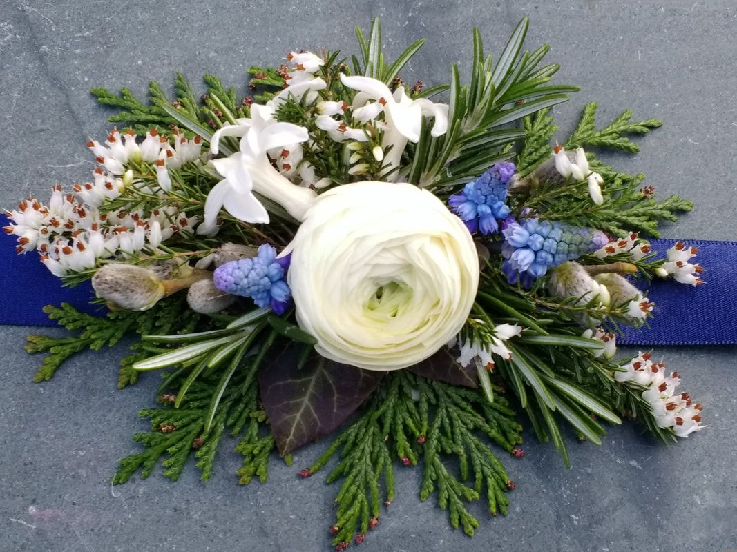 Wrist corsage made from spring flowers in white & blue