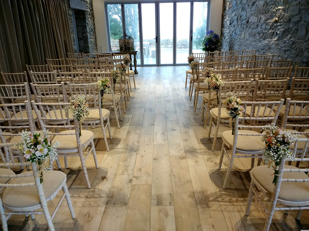 GG's Yard Wedding Ceremony venue with wedding flowers decorating chairs by Galloway Flowers