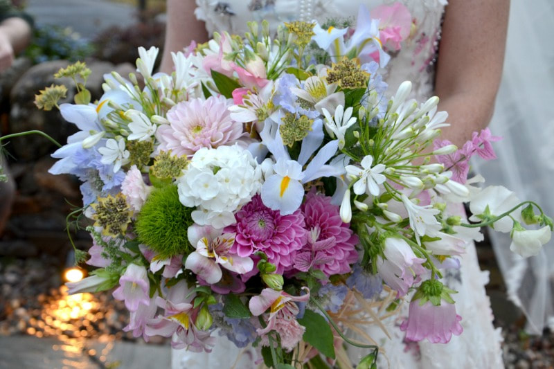 Pretty pastel bridal bouquet of summer flowers for a July wedding